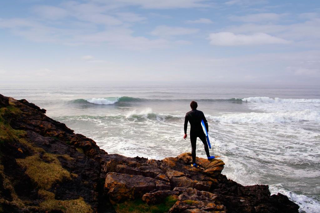 Surfer looks at waves at Tullan Strand, Bundoran, County Donegal, Ireland